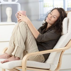 12174604 - woman relaxing with closed eyes and cup of tea in armchair at home, daydreaming.